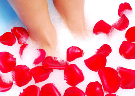 spume: woman legs in spume with rose petal