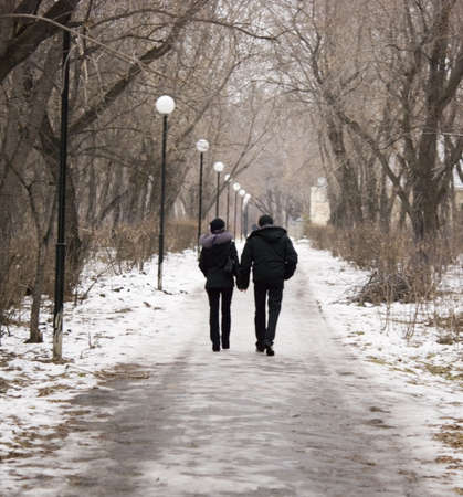 winter wedding: a couple walking in park Stock Photo