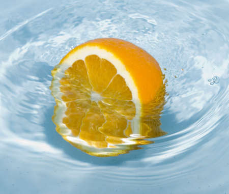 orange fruit in water splash photo