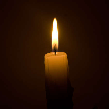 burning candle over black background
