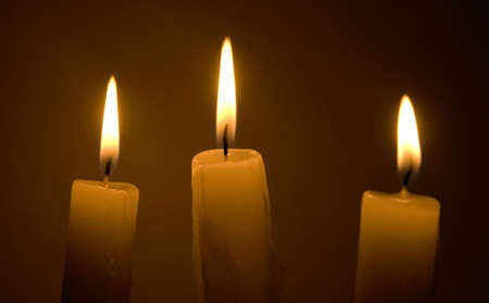 three candles over black background photo