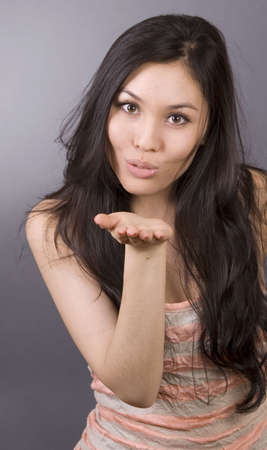 young woman blow a kiss over grey background photo