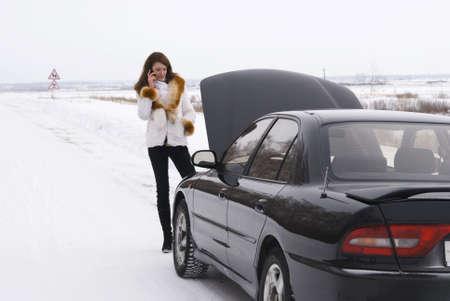 broken car: mujer joven hablando por un tel�fono celular, tratando de obtener ayuda con su coche roto. Foto de archivo