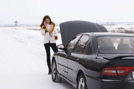 winter break: young woman talking on a cell phone, trying to get help with her broken car.
