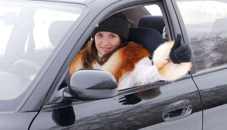 Young woman sits in the car and shows ok sign. photo