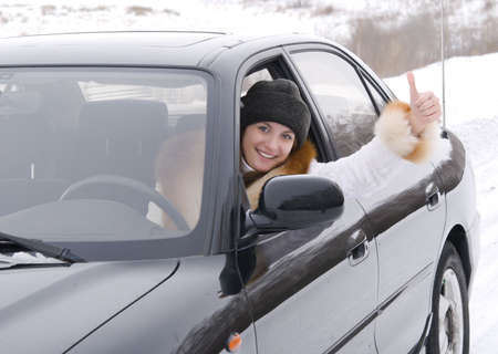 young woman sits in the car and shows ok sign