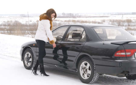 young beautiful woman opening her car photo