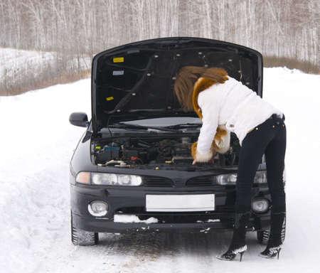 junge Frau mit kaputten Auto