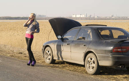 young woman talking on a cell phone, trying to get help with her broken car Stock Photo - 4705492