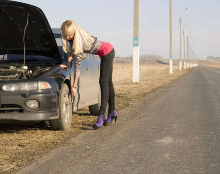 young pretty blonde with her broken car Stock Photo