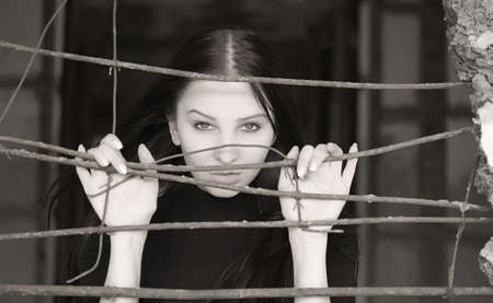 young pretty woman behind iron grid photo