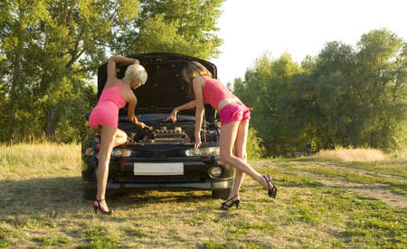 two young pretty woman repairing the car photo