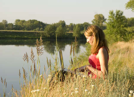 young woman with notebook on the river bank photo
