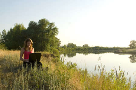junge hübsche Frau mit Notebook am Ufer des Flusses