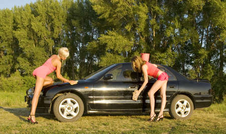 two young pretty woman wash the car photo