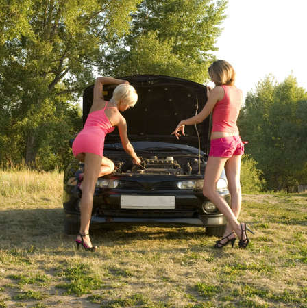 two young pretty woman with broken car photo