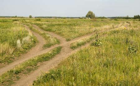 Straßenkreuzung und grünes Gras und blauer Himmel Standard-Bild