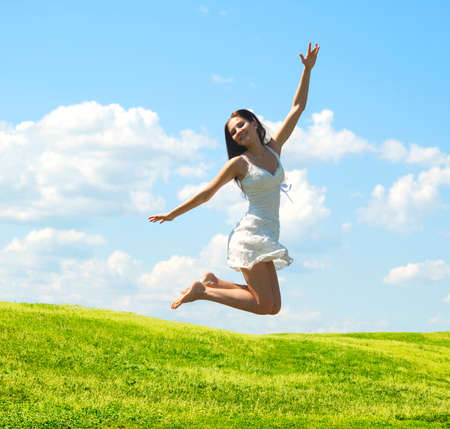 vitality: jumping happy woman against nature background Stock Photo