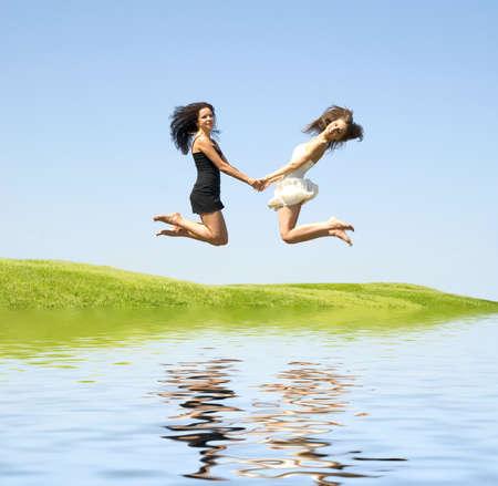 Springen zwei glückliche Frau über Himmel Lizenzfreie Bilder