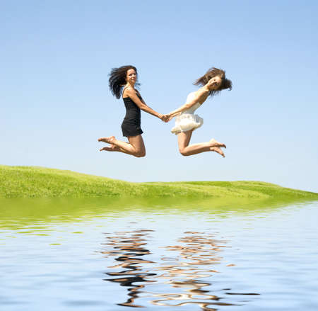two happy jumping woman over sky