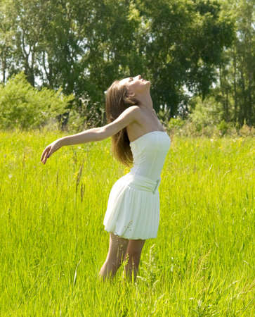 young pretty woman enjoing in green field photo