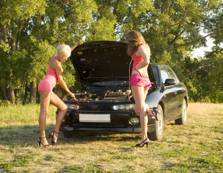 two young pretty woman repairing car photo