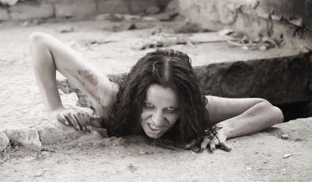 witch face: scary woman creeping out of a hole Stock Photo