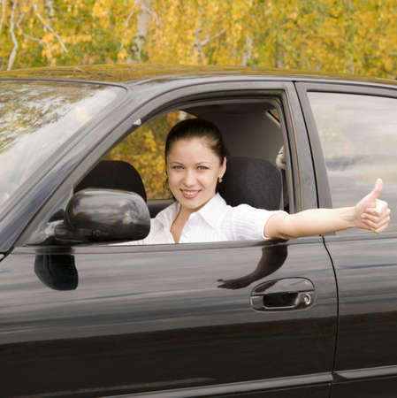 young happy woman driving her car photo