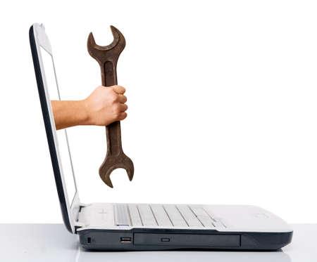 Hand mit Schraubenschlüssel kommt von Notebook-Bildschirm