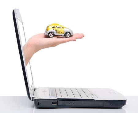 Hand mit Auto kommt von Notebook-Bildschirm auf weiß isoliert