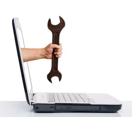 hand met moer sleutel afkomstig van lap top scherm