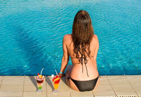 young pretty woman sitting in a swimming pool photo