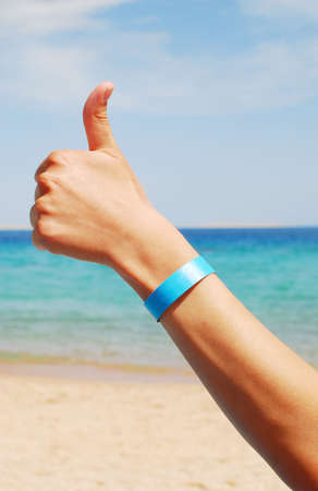 inclusive: hand with all inclusive bracelet over sea background