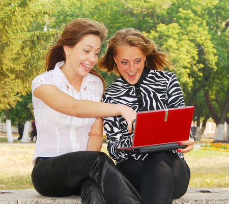 surprised two young girlfriends looking in laptop  photo