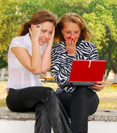 surprised two girlfriends  looking in laptop  photo