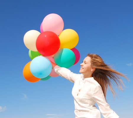 jonge tevreden vrouw met ballonnen over hemel