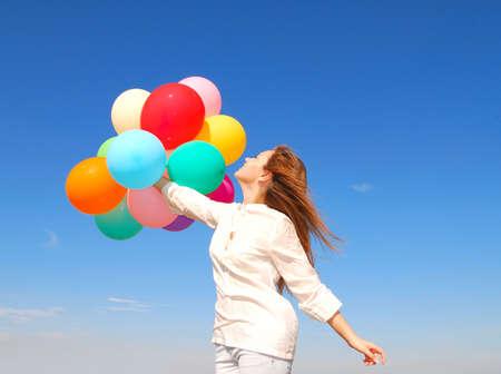 Gelukkig jonge vrouw met ballonnen over hemel