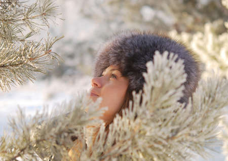 young pretty woman in winter forest photo