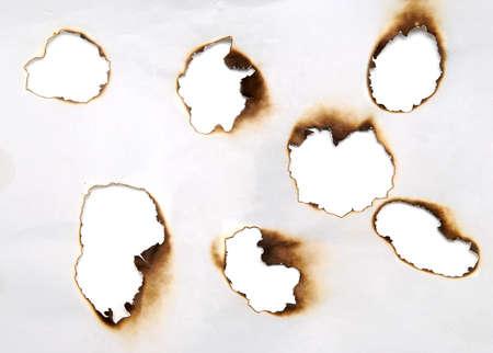 quemado: agujeros quemados en un documento Foto de archivo