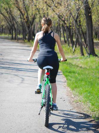 junge Frau Fahren Fahrrads in einem park Standard-Bild