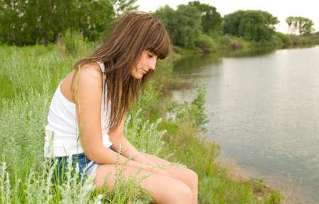 sad woman at the bank of river photo
