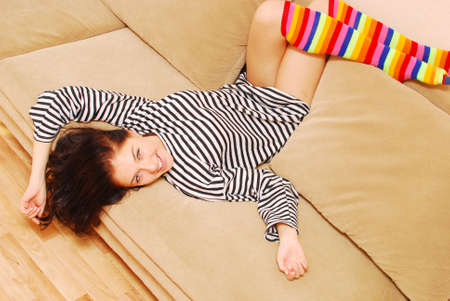 striped shirt: happy young girl on a sofa