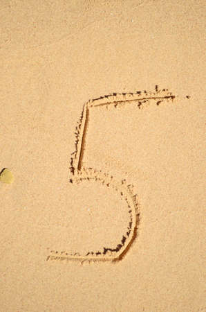 number five written on the sand photo
