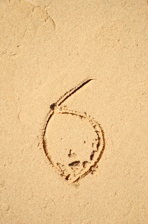 number six written on the sand photo