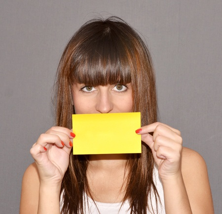woman holding an yellow card, covering her mouth  photo