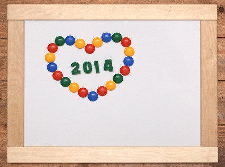 number 2014 with heart on wooden frame photo