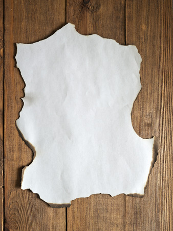 burnt paper: burnt paper on a wooden background