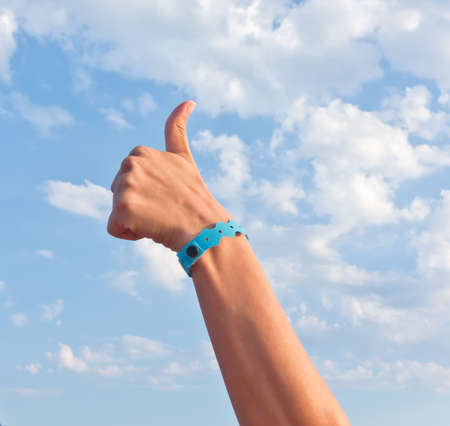 inclusive: hand with all inclusive bracelet over sky