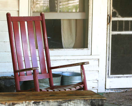 rocking: Red Rocking Chair on the Porch of an Old Farmhouse Stock Photo