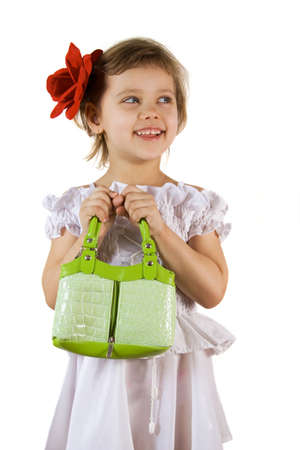 Little smiling girl with green bag and red rouses in the hair